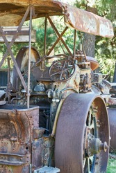 A vertical shot of an old metallic tractor in the garden