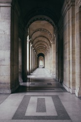 A vertical shot of an outdoor hallway of a historic building with outstanding architecture