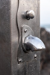 A vertical shot of an outdoor water tap with waterdrops on the metal surface