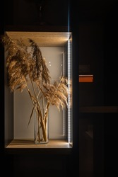 A vertical shot of artificial sheaves of wheat in a glass vase on a shelf with lights