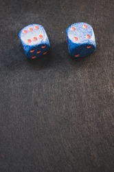 A vertical shot of blue dice on a black surface under the lights
