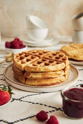 A vertical shot of delicious waffles with vanilla ice cream, strawberries and raspberries on a breakfast table