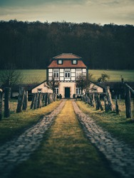 A vertical shot of pathway with wooden post barriers to an old rural house on a gloomy day