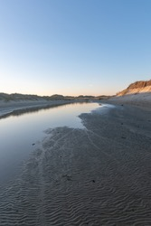 A vertical shot of pond in the middle of sandy coast in the evening in Norderney