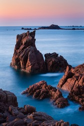 A vertical shot of rock formations in the beautiful clear blue sea in Guernsey