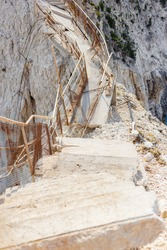 A vertical shot of ruined narrow stone stairs on a mountain rock