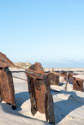 A vertical shot of shipwrecks on a sandy beach in Norderney