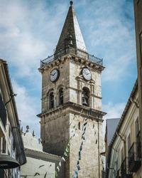 A vertical shot of the tower bells and big clock of Saint Santiago church in Villena city, Alicante, Spain