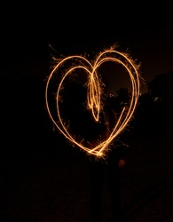 A vertical sparkler painting of the shape of a heart isolated on a black background