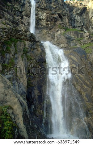 A vertical stone slope and a majestic impetuous waterfall. #638971549