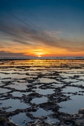 A vertical view of a beautiful sunset over the ocean with rocky beach and tidal pools in the foreground