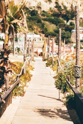 A vertical view of a narrow passageway leading inland from the beach with wooden flooring and posts connected with a rope, shallow depth of field, selective focus in the middle foreground, sunny day