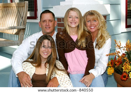 A very attractive family on the front porch of their home.