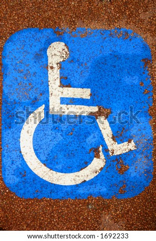 A very battered sign for disabled parking, on red tarmac, giving an impression of disablility (look at the damaged knee).