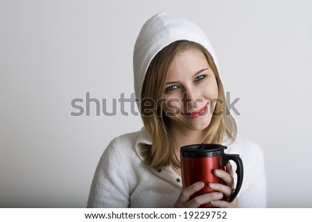 A very beautiful young model is smiling while holding a red holiday thermos
