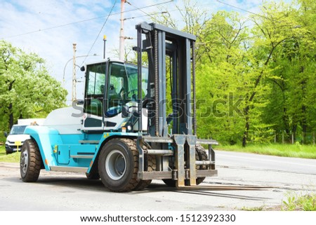 A very big and powerful turquoise high-capacity pneumatic super-heavy-duty rough terrain forklift parked on the street next to a lush green park on a nice summer day, waiting for work.
