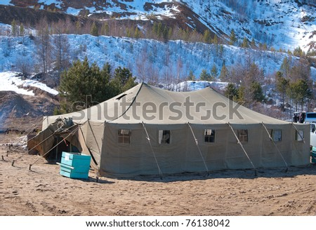a very big military tent at a mountain foot