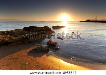 A very bright sunrise over a Mediterranean rocky seascape.