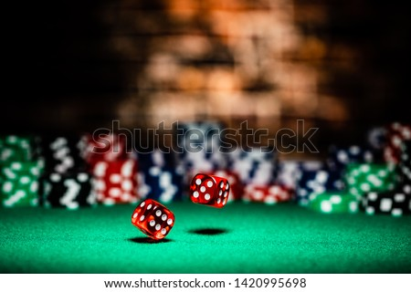 A very close up shot of 2 dice rolling on a green felt table top in very crisp focus, showing 4, 5 and 6 on the faces.