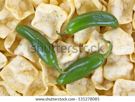 A very close view of jalapeno peppers on top of potato chips with jalapeno seasoning.