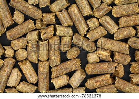 A very close view of smoke flavoring pellets for barbecue on a black background.