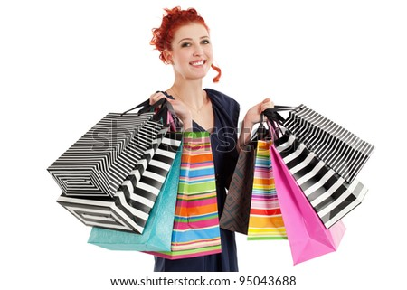 A very happy shopaholic girl holding many shopping bags and smiling about her rabid purchases.