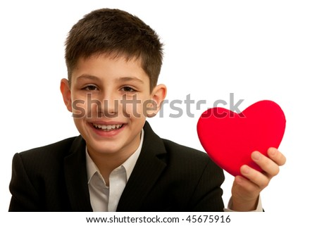 A very happy smiling boy is showing a red heart; isolated on the white background