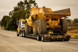 A very large haul dump truck being hauled by an 18 wheel truck down a freeway