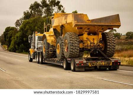 A very large haul dump truck being hauled by an 18 wheel truck down a freeway Сток-фото ©