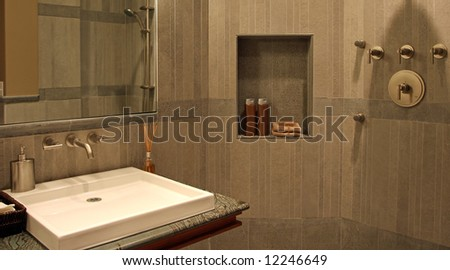 A very modern bathroom with stone walls and a flat sink.