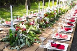 A very nicely decorated wedding table appointments with beautiful decor with plates and serviettes in spring garden. Beautiful flowers on table in wedding day. The elegant dinner table.