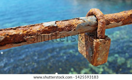 A very old and rusty love lock or padlock  on a section of the chain link fence, symbol of unbreakable love and lifetime commitment for the couples who decided to eternally lock their hearts together