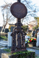A very old, rusted forged decoration on an abandoned grave - the figure of the Virgin Mary