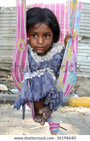A very poor sick Indian girl sitting in a swing made of an old sari (traditional women clothes).