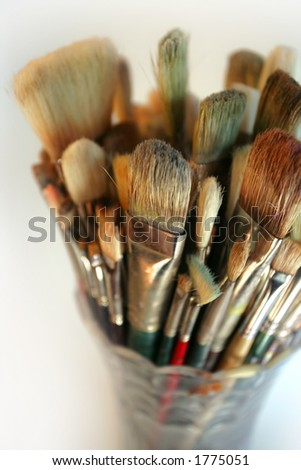 A very shallow depth-of-field image of used paintbrushes stacked in a glass vase. Focus is on the front brushes.
