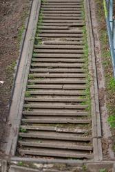 a very steep staircase  next to dark sand