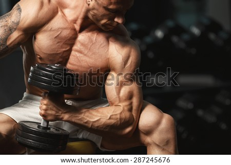 A very strong young guy bodybuilder, doing exercises with dumbbells in the gym. Fitness muscular body on dark background