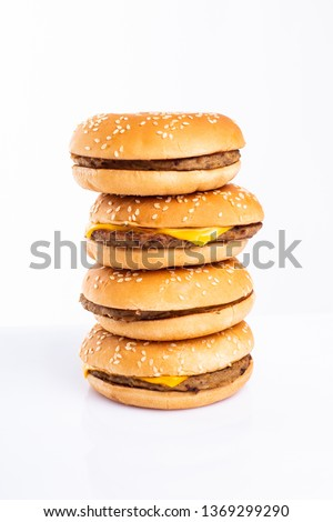a very tall pile of cheesburgers isolated over a white background