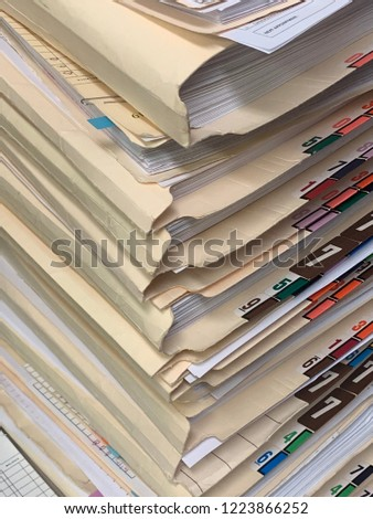 A very tall stack of paper patient records from a medical clinic or office in a vertical image format.