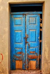 A very worn and battered old blue door locked with a rusty chain situated on the Greek isle of Crete.