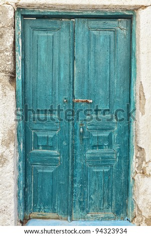 A very worn and battered old blue door situated on the Greek isle of Santorini.