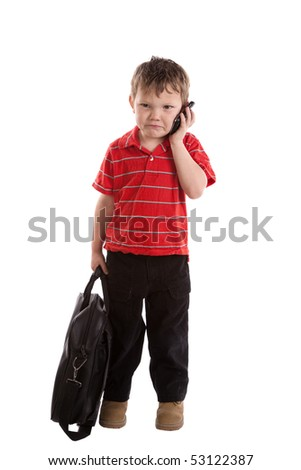 A very young boy has a black bag is is frustrated and talking on his cell phone.
