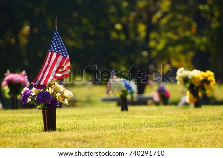 A veteran's grave decorated with an American flag in honor of their service and sacrifice.