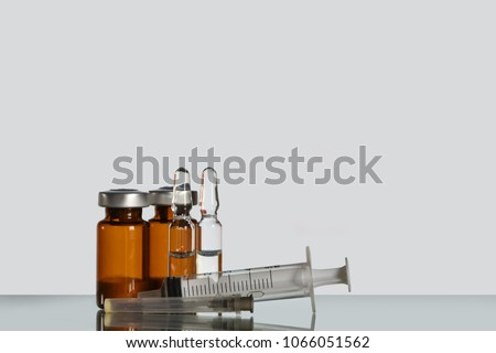 A vial (ampoule, container) with a drug (medicine powder) on a white background. Medical injection syringe. #1066051562