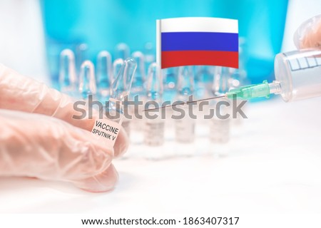 A vial with Russian anti covid-19 (Sars-CoV-2) vaccine called Sputnik V (Gam-COVID-Vac, trade-named Sputnik V) with a syringe and a Russian flag in a background