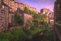 A vibrant colourful sunset or sunrise view of historic old town Dean Village and Water of Leith in Edinburgh, Scotland in Spring.