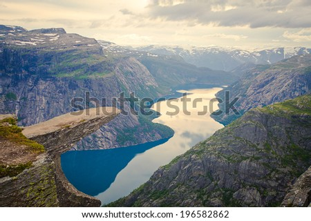 A vibrant picture of famous norwegian hiking place trolltunga the trolls tongue rock skjegedall with a tourist and lake ringedalsvatnet and mountain panoramic scenery epic view Norway