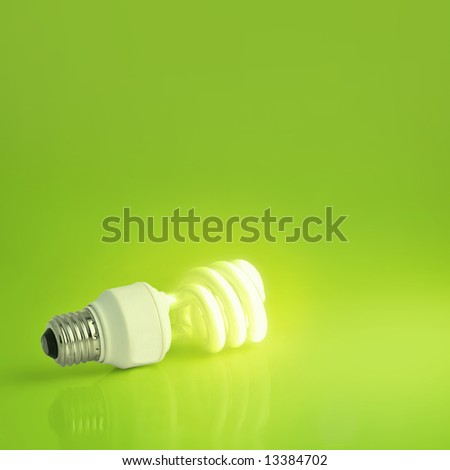 A vibrant presentation of a modern energy-saving lightbulb lit on a lush green background.  Plenty of copyspace, ideal for ecology, energy concepts or imagination and marketing pitches