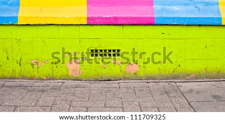 A vibrant wall next to a pavement showing damage