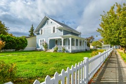 A Victorian cottage with a white picket fence and covered front porch and deck in the Spokane, Washington area of the Inland Northwest, USA.
